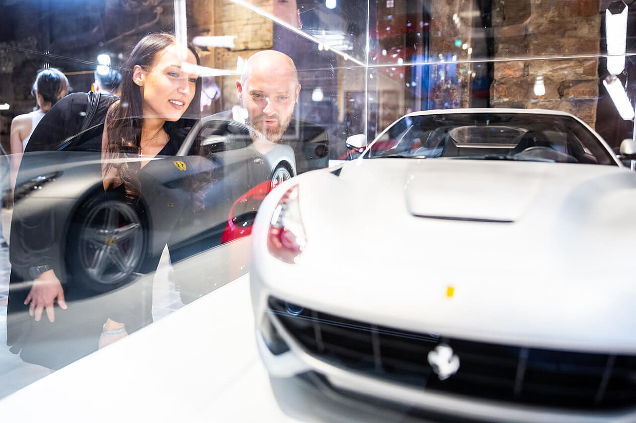 Visitors in front of a Ferrari model